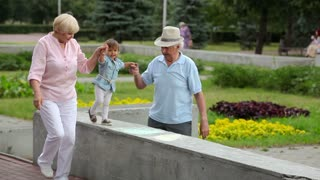 Little girl making a step after step holding hands with her grandparents