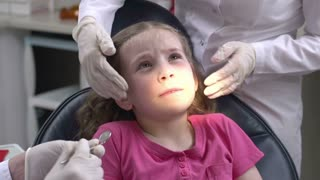 Little girl stressed at dental check-up, her head held by assistant and tongue obstructing visional access to doctor