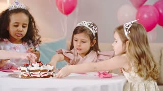 Little girls in fancy dresses and tiaras moving plate with birthday cake and eating strawberries and whipped cream from top of it