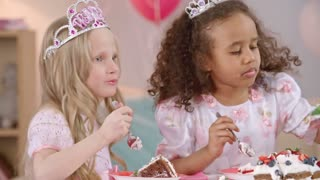 Little girls with whipped cream on their faces dressed like princesses eating delicious birthday cake with spoon at the table