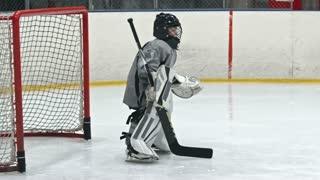 Little goaltender trying to prevent the opposing team from scoring but falling down on ice rink