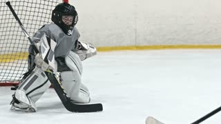 Little hockey goaltender in protective uniform falling down on ice rink while playing the game