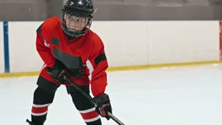 Little hockey player standing on ice rink and shooting the puck into the net