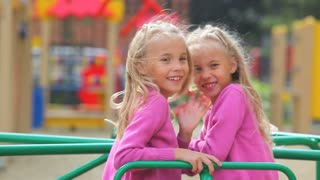 Little twin girls posing on carousel