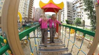 Little twins walking over child�s bridge