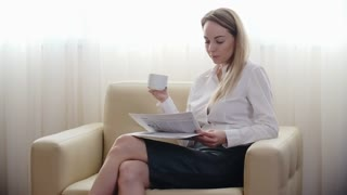 Lockdown of businesswoman in formal clothes sitting with crossed legs on chair in hotel room reading newspaper and drinking coffee