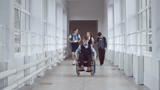 Lockdown of concentrated and sad looking schoolboy in wheelchair wearing uniform and glasses slowly riding along hallway at recess, three other schoolchildren chatting and walking past without noticing him