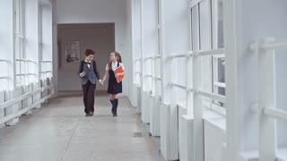 Lockdown of excited schoolboy in uniform telling story to happy schoolgirl with notebooks and walking hand in hand along school hallway