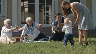 Lockdown of mother helping blond toddler boy to walk towards encouraging grandparents and father on picnic in backyard