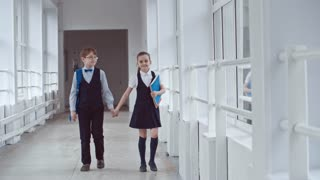 Lockdown of schoolboy in uniform and glasses holding hand of schoolgirl with notebooks chatting and walking along hallway in school