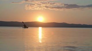 Lockdown of silhouette of tourist slowly paddling kayak across lake under setting sun
