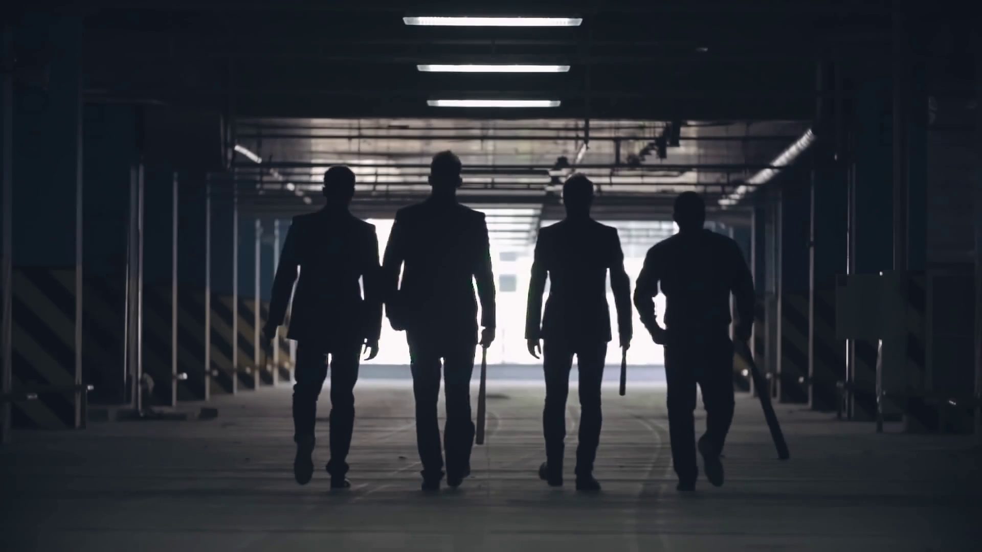 Lockdown of silhouettes of four confident men in suits holding baseball bats walking towards exit of parking lot Stock Video Footage - Storyblocks