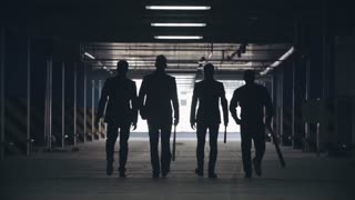 Lockdown of silhouettes of four confident men in suits holding baseball bats walking towards exit of parking lot