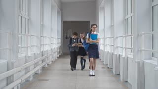 Lockdown of smiling schoolgirl in uniform with course books and glasses walking along school hallway, three other schoolchildren in uniform walking behind smiling and discussing book