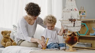 Lockdown shot of curly toddler and mother looking at ship model and playing with wooden giraffes toys