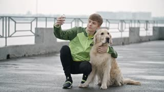 Lockdown wide shot of teenage boy in windcheater sitting on embankment with his golden retriever dog petting him and taking selfie