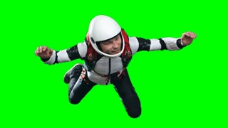 Locked down slow motion shot of exhilarated man in helmet and parachuting gear flying in free fall, green background chroma key, extreme sports concept