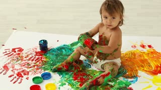 Lovely toddler having a good time making a mess of finger paints