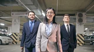 Low angle medium shot of smiling Asian businesswoman with folder in hands and two confident young businessmen in formalwear walking in underground parking of office building