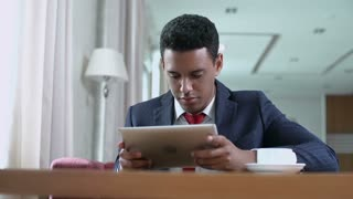 Low angle shot of businessman with digital tablet sitting alone in cozy coffee-shop