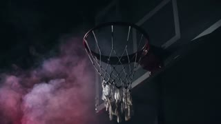 Low angle view of man throwing ball into basketball hoop in slow motion in the darkness with red smoke in the background