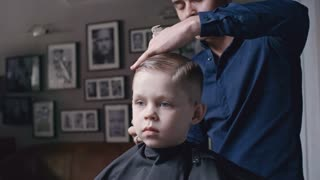 Male barber using comb and scissors while making a haircut for little boy