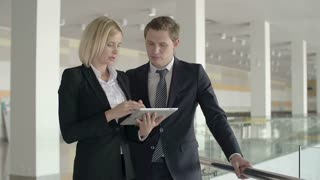 Male boss and female subordinate scheduling affairs on graphic PDA in large light hall
