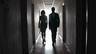 Man and woman passing by the room doors of hotel in the dark