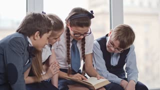 Medium shot of four schoolchildren wearing uniform sitting in school hallway on windowsill at recess reading aloud from book and laughing