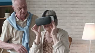 Medium shot of laughing senior man standing beside elderly woman in virtual reality glasses dancing with excitement and enjoying experience
