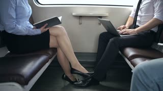 Mid-section of man and woman seated in train facing each other and busy reading and laptop working