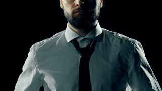 Mid-section of man putting his tie on in the dark