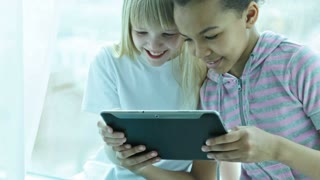 Modern preteen girls watching interesting staff on the screen of the touchpad