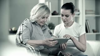 Monochrome shot of young girl helping senior woman use the touchpad