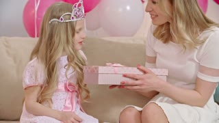Mother giving birthday present to her cute blonde daughter dressed like princess, kissing and hugging her