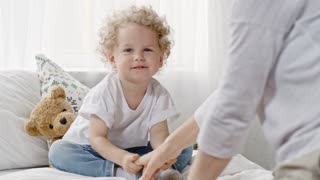 Mothers hand tickling blond haired curly baby in jeans