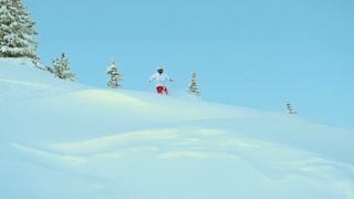 Mountain skier jumping in fresh snow powder and riding down the slope