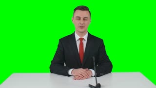 Newsman sitting in studio at the desk with microphone and telling some information on green screen background