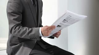 Office worker reading financial news in daily paper
