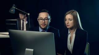 Pair of businesspeople in formalwear, man and woman, sitting in dark office at desk looking at computer screen and discussing business issues, nodding and gesturing, while third man is out of focus at his desk