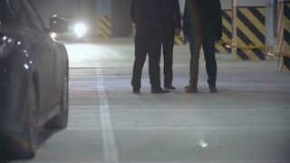 PAN of unrecognizable mafia man talking in parking lot and then walking away and getting into car, human hand sticking out of vehicle trunk