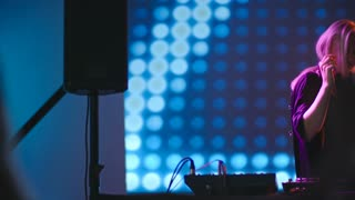 PAN with slow motion of beautiful blond DJ woman dancing behind mixer, LED video wall in background