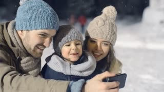 Panning shot of young family laughing and video calling someone in park on snowy winter evening