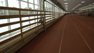 POV of running tracks inside the stadium; athlete jogging towards the camera