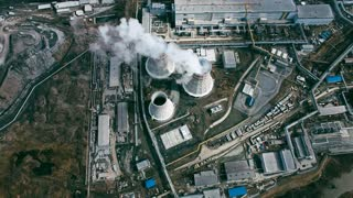Power plant with cooling towers rejecting waste heat to atmosphere and producing steam surrounded by factories in large industrial area, aerial view