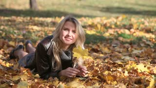 Pretty blonde lying on the fallen leaves in park catching the last glimpses of the autumn sun