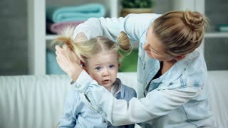 Pretty woman doing her daughter�s hair