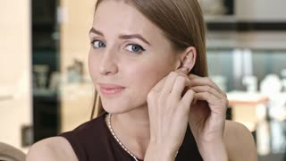Pretty young lady trying on diamond stud earrings in silver and looking at the camera with smile
