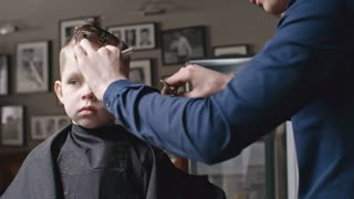 Professional barber combing and cutting hair of little boy with scissors