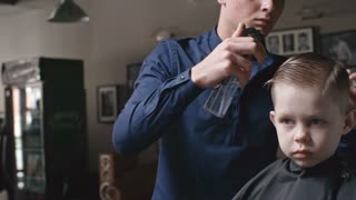Professional barber spraying water on the hair of his little client and brushing it with comb